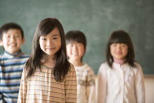 黒板の前で微笑む小学生の写真素材 [FYI04555025]