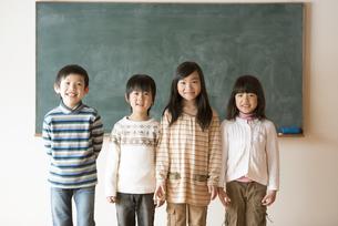 黒板の前で微笑む小学生の写真素材 [FYI04555034]
