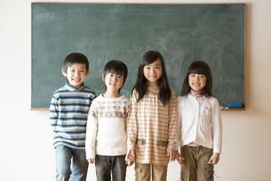 黒板の前で微笑む小学生の写真素材 [FYI04555035]