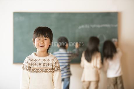 黒板の前で微笑む小学生の男の子の写真素材 [FYI04555042]