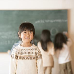 黒板の前で微笑む小学生の男の子の写真素材 [FYI04555043]