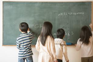 黒板にアルファベットを書く小学生の写真素材 [FYI04555045]