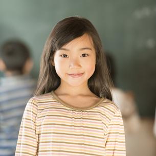 黒板の前で微笑む小学生の女の子の写真素材 [FYI04555048]