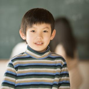黒板の前で微笑む小学生の男の子の写真素材 [FYI04555050]