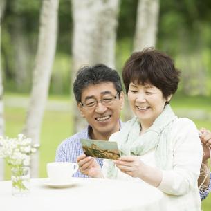絵はがきを見るシニア夫婦の写真素材 [FYI04555084]