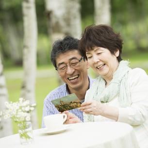 絵はがきを見るシニア夫婦の写真素材 [FYI04555085]
