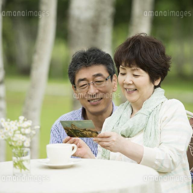 絵はがきを見るシニア夫婦の写真素材 [FYI04555089]