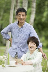 絵はがきを持ち微笑むシニア夫婦の写真素材 [FYI04555098]