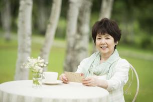 絵はがきを持ち微笑むシニア女性の写真素材 [FYI04555101]