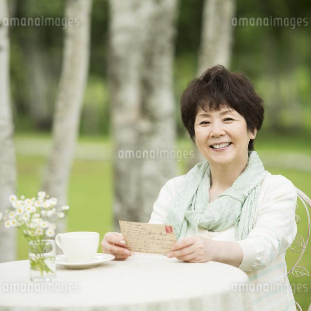 絵はがきを持ち微笑むシニア女性の写真素材 [FYI04555106]