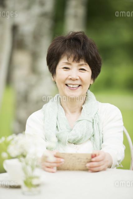 絵はがきを持ち微笑むシニア女性の写真素材 [FYI04555107]