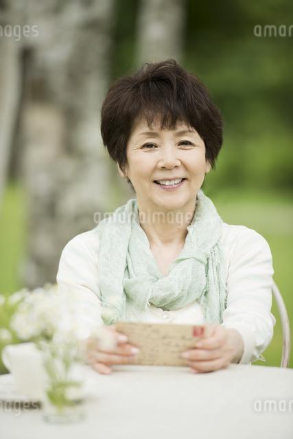 絵はがきを持ち微笑むシニア女性の写真素材 [FYI04555108]