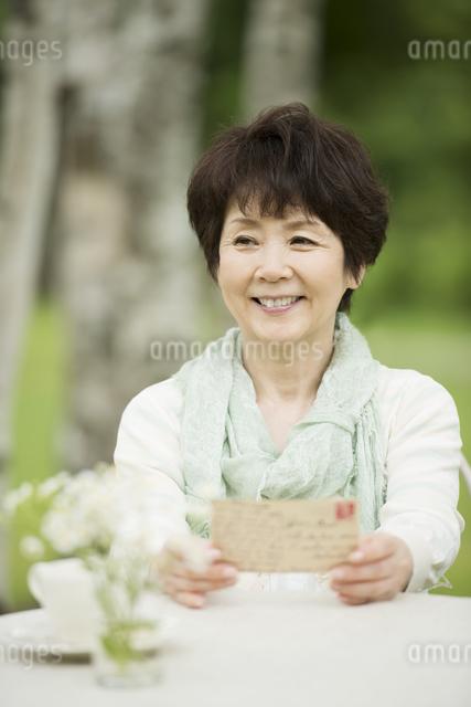 絵はがきを持ち微笑むシニア女性の写真素材 [FYI04555109]