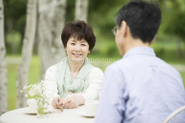 絵はがきを持ち談笑をするシニア夫婦の写真素材 [FYI04555119]