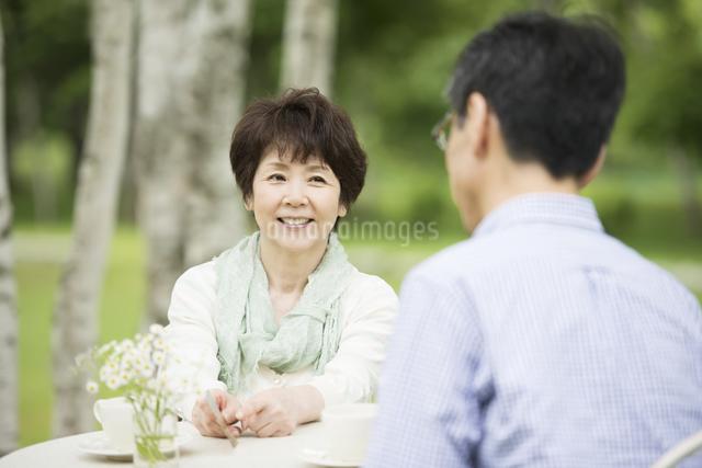 絵はがきを持ち談笑をするシニア夫婦の写真素材 [FYI04555120]