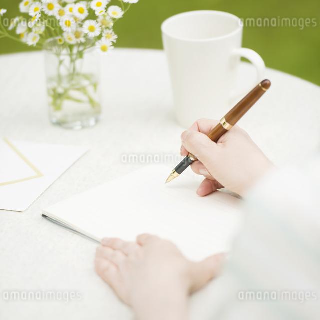 手紙を書くシニア女性の手元の写真素材 [FYI04555193]