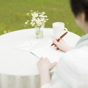 手紙を書くシニア女性の手元の写真素材 [FYI04555197]