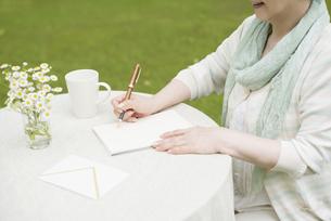 手紙を書くシニア女性の手元の写真素材 [FYI04555199]