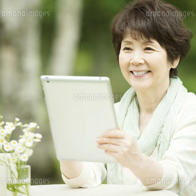 タブレットPCを持ち微笑むシニア女性の写真素材 [FYI04555207]