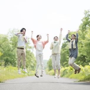 一本道でジャンプをする大学生の写真素材 [FYI04555311]