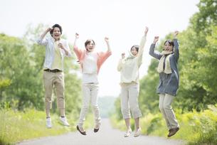 一本道でジャンプをする大学生の写真素材 [FYI04555314]