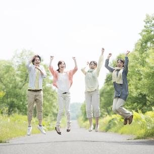 一本道でジャンプをする大学生の写真素材 [FYI04555315]