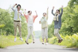 一本道でジャンプをする大学生の写真素材 [FYI04555318]