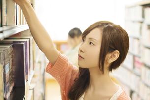 図書館で本を選ぶ女性の写真素材 [FYI04555368]