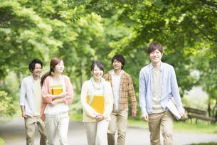 新緑の中を歩く大学生の写真素材 [FYI04555396]