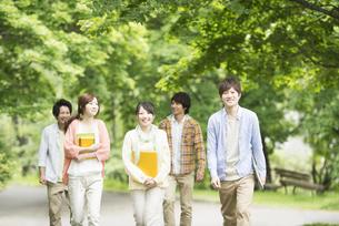 新緑の中を歩く大学生の写真素材 [FYI04555397]