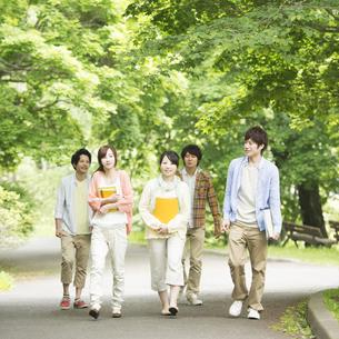 新緑の中を歩く大学生の写真素材 [FYI04555404]