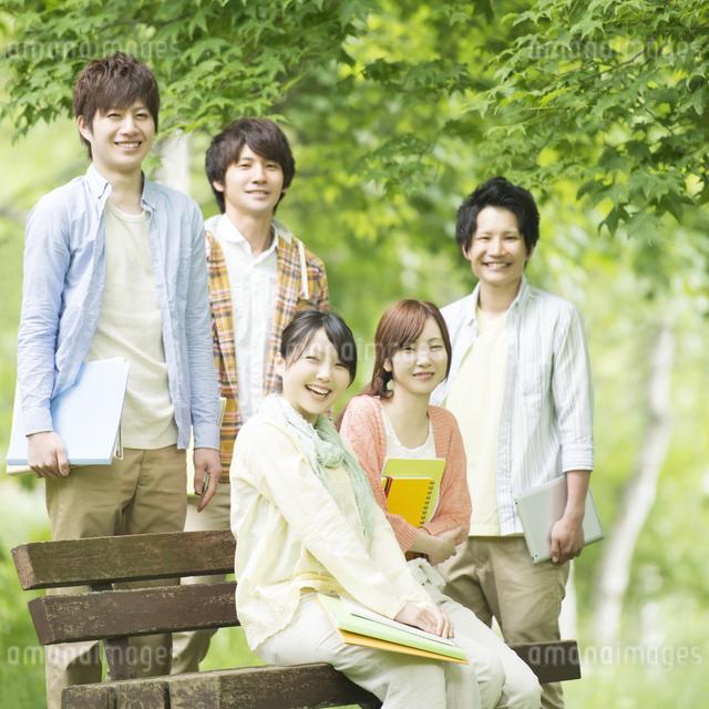 新緑の中で微笑む大学生の写真素材 [FYI04555411]