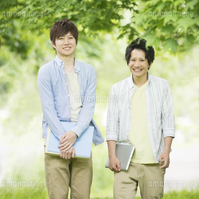 新緑の中で微笑む大学生の写真素材 [FYI04555418]