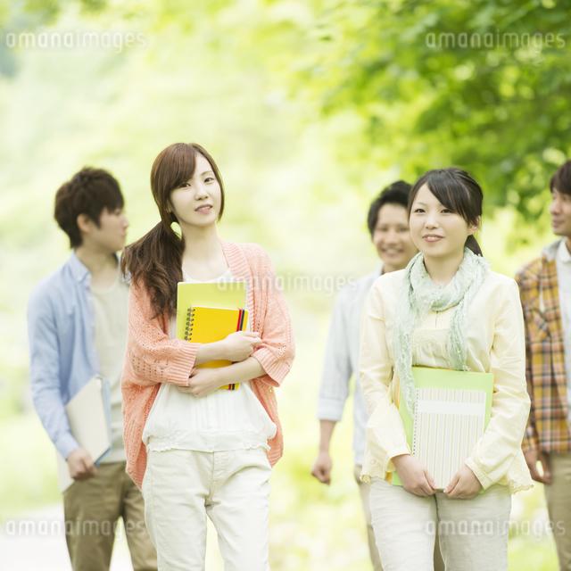 新緑の中を歩く大学生の写真素材 [FYI04555419]