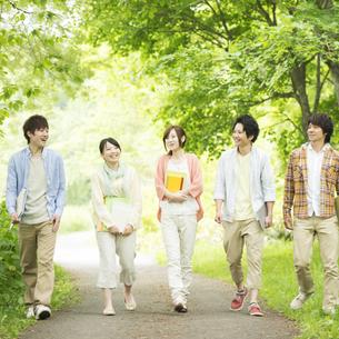 新緑の中を歩く大学生の写真素材 [FYI04555438]
