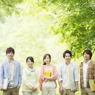 新緑の中で微笑む大学生の写真素材 [FYI04555439]