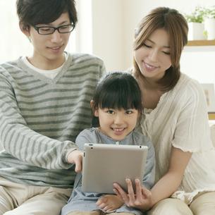 タブレットPCを持ち微笑む親子の写真素材 [FYI04555442]