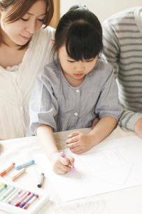 お絵描きをする女の子と両親の写真素材 [FYI04555477]