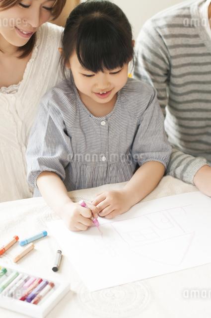 お絵描きをする女の子と両親の写真素材 [FYI04555478]