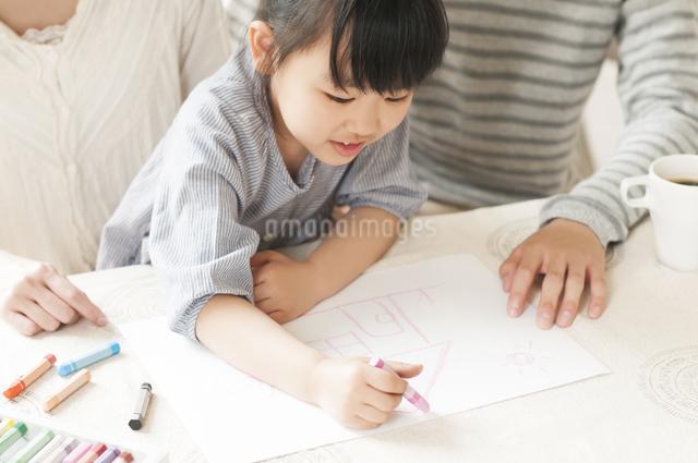 お絵描きをする女の子と両親の写真素材 [FYI04555479]