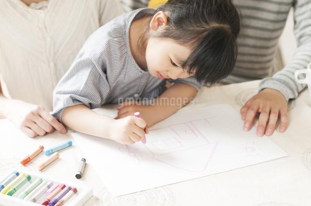 お絵描きをする女の子と両親の写真素材 [FYI04555480]