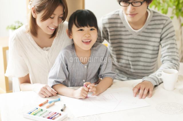 お絵描きをする女の子と両親の写真素材 [FYI04555481]