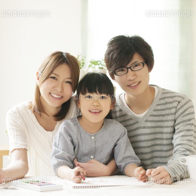 お絵描きをする女の子と両親の写真素材 [FYI04555486]