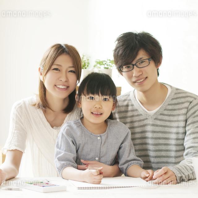 お絵描きをする女の子と両親の写真素材 [FYI04555487]