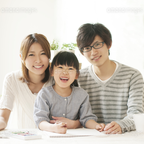 お絵描きをする女の子と両親の写真素材 [FYI04555488]