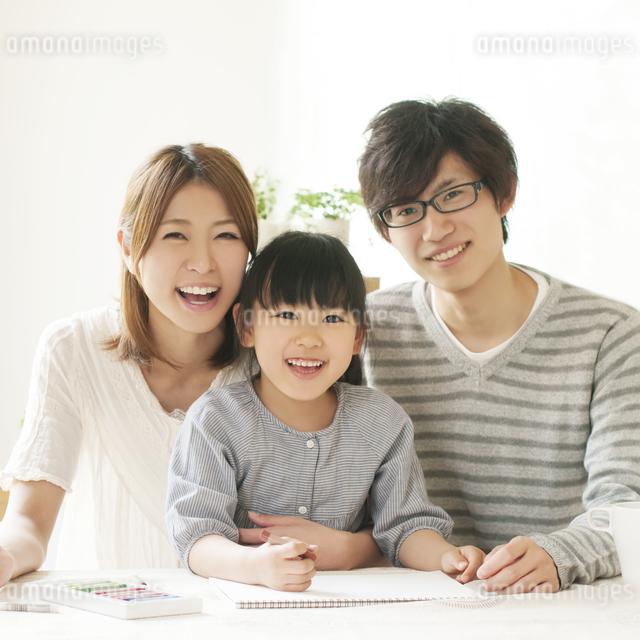 お絵描きをする女の子と両親の写真素材 [FYI04555489]