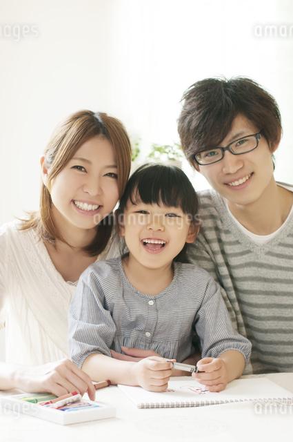 お絵描きをする女の子と両親の写真素材 [FYI04555490]
