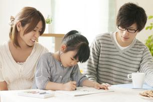 お絵描きをする女の子と両親の写真素材 [FYI04555491]