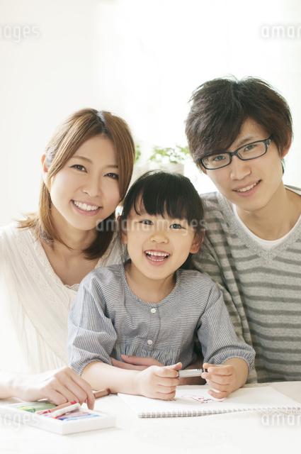 お絵描きをする女の子と両親の写真素材 [FYI04555492]