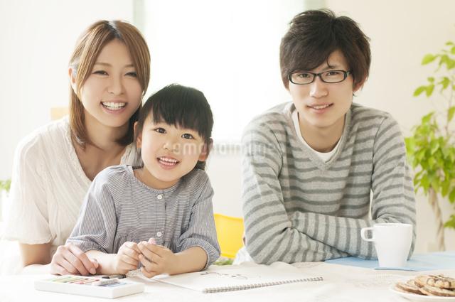 お絵描きをする女の子と両親の写真素材 [FYI04555493]